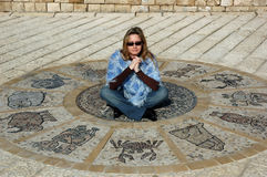 Astrological wheel. Blond woman sitting on antic astrological wheel Stock Photo