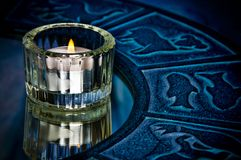 Astrology. Symbolized with blue zodiac and candle standing on reflecting surface Royalty Free Stock Photography