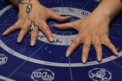 Astrology. Female hands over astrological background royalty free stock photography