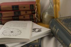 Astrology books and hourglass in psychic office. Astrology books, natal charts and hourglass in psychic office in Belgrade apartment, Serbia royalty free stock photography