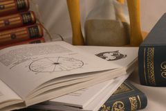 Astrology books and hourglass in psychic office. Astrology books, natal charts and hourglass in psychic office in Belgrade apartment, Serbia stock images