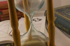 Astrology books and hourglass in psychic office. Astrology books, natal charts and hourglass in psychic office in Belgrade apartment, Serbia stock photo