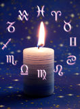 Astrology and candle. A candle in center of astrological wheel on blue Christmas background stock images