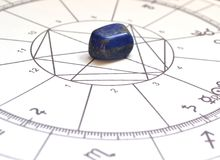 Astrology chart  Lapis Lazuli Natural stone Crystal Natal chart. Astrology chart with a  Lapis Lazuli crystal. Natural stone in the center.  Natal chart in the Stock Photo