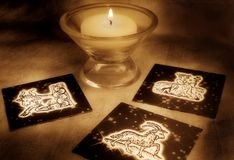 Astrology earth signs. Candle and astrology cards with the earth signs symbols Capricorn, Virgo, Taurus Stock Photo