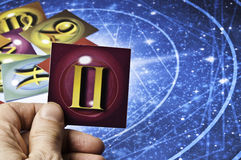 Astrology Gemini. Hand holding an astrology card with symbol of sign of Gemini royalty free stock photo