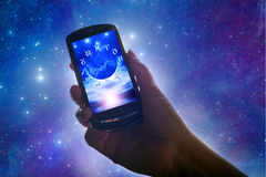Astrology on-line. Female hand holding a cell phone with astrological background like a concept for on-line horoscope Royalty Free Stock Photo