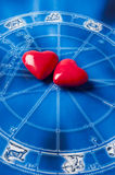 Astrology and love. Two red hearts over blue zodiac like a astrology concept for Valentine´s Day royalty free stock images