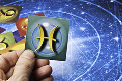 Astrology Pisces. Hand holding an astrology card with symbol of sign of Pisces stock photos