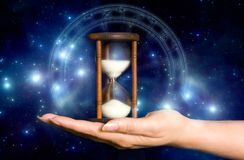 Astrology and time. Female hand keeping hoir-glass over blue mystical background with stars and astrological horoscope like a concept for astrology and mystical Stock Photos