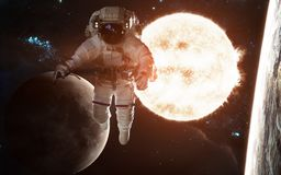 Astronaut on background of the Sun. Solar system. Earth and moon. Elements of the image were furnished by NASA. Astronaut on background of the Sun. Solar system royalty free stock images