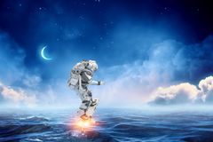 Astronaut on board. Mixed media. Spaceman on flying board surfing the sea. Mixed media Stock Photos