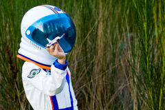 Astronaut boy playing with a toy airplane Stock Image