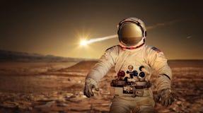 Astronaut, der die Oberfläche des roten Planeten Mars erforscht lizenzfreies stockbild