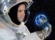 Astronaut, der kleine Planetenerde schaut Lizenzfreies Stockfoto