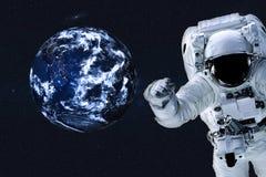 Astronaut dichtbij de Aardeplaneet stock fotografie