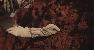 Astronaut die rots op Mars onderzoeken stock video