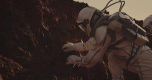 Astronaut die rots op Mars onderzoeken stock videobeelden