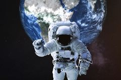 Astronaut in einer Front des Erdplaneten stockbilder