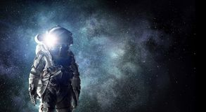 Astronaut explorer in space. Mixed media. Astronaut against dark night sky background. Mixed media Royalty Free Stock Image