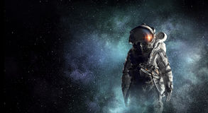 Astronaut explorer in space. Mixed media. Astronaut against dark night sky background. Mixed media Royalty Free Stock Photography