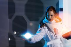 Astronaut explores the hologram of the new planetary system. Portrait of a woman astronaut in a space suit, dreamy look up Stock Photo