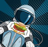 Astronaut with fast food hamburger in pop art style. Cosmonaut on blue background eating cheeseburger Royalty Free Stock Photography