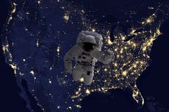 Astronaut flying in open space over the USA during night, near earth. Image made of NASA photos f stock image