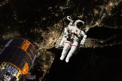Astronaut flying in open space over the USA during night, near earth. Image made of NASA photos f. Astronaut flying in open space over the USA during night, near royalty free stock photo
