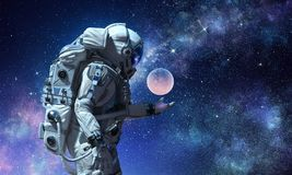 Spaceman and his mission. Mixed media. Astronaut holding moon planet in palm. Elements of this image furnished by NASA Royalty Free Stock Image