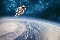 Astronaut im Weltraum gegen den Hintergrund der Planetenerde Taifun über Planet Erde lizenzfreie stockfotos
