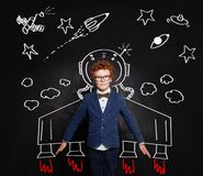 Astronaut kid. Smart child boy spaceman on blackboard background with space pattern.  royalty free stock photo