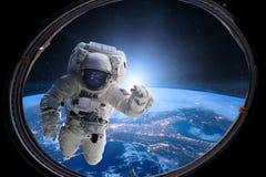 Astronaut in kosmische ruimte van patrijspoort op achtergrond van de Aarde Elementen van dit die beeld door NASA wordt geleverd royalty-vrije stock foto's