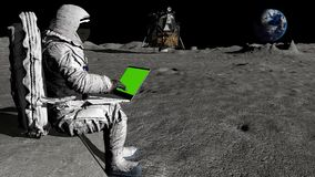 Astronaut on the moon typing on a laptop with a green screen.