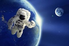 Astronaut oder Raumfahrer, die in Raum mit Erdplaneten- und -mondhintergrund schwimmen lizenzfreies stockfoto