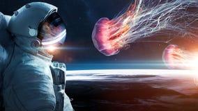 Astronaut in orbit meets jellyfish. stock images