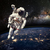 Astronaut in outer space above the earth during night time. Elem Royalty Free Stock Photos