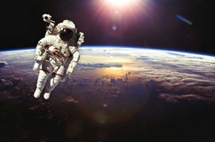 Astronaut in outer space above the earth during sunset. Elements Stock Images