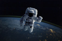 Astronaut in outer space. Background Earth. Elements of this image furnished by NASA stock images