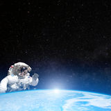 Astronaut in outer space behind the planet earth Royalty Free Stock Image