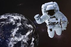 Astronaut in outer space near night Earth. Astronaut in outer space with Earth planet of solar system. Science fiction wallpaper. Elements of this image were royalty free stock image
