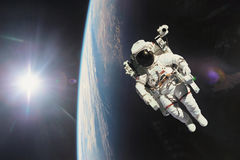 Astronaut in outer space with planet earth as backdrop. Elements stock image