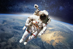 Astronaut in outer space with planet earth as backdrop. Elements Stock Photos