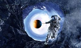 Fantasy image with spaceman catch planet. Mixed media. Astronaut in outer space pulling planet on rope. Elements of this image are furnished by NASA stock images