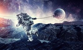Fantasy image with spaceman catch planet. Mixed media. Astronaut in outer space pulling planet on rope. Elements of this image are furnished by NASA stock photos