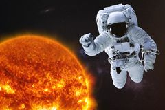 Astronaut in outer space with Sun of solar system with reflection in helmet. Science fiction wallpaper. Astronaut in outer space with Sun of solar system royalty free stock photo