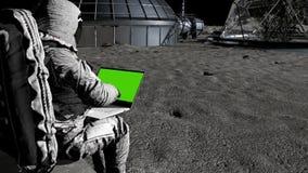 Astronaut på månen som skriver på en bärbar dator med en grön skärm stock illustrationer