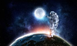 Spaceman and his mission. Mixed media. Astronaut pointing with finger on moon planet. Elements of this image furnished by NASA Stock Images