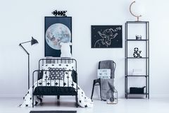 Astronaut poster in kid`s bedroom. White globe on the shelf next to a chair with blanket and astronaut poster in kid`s bedroom interior with bed stock images