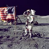 Astronaut saluting American flag on moon Stock Photo